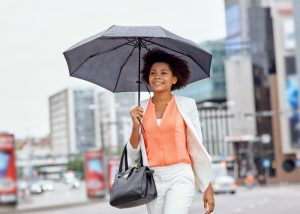 Professional woman holding an umbrella walking with good posture