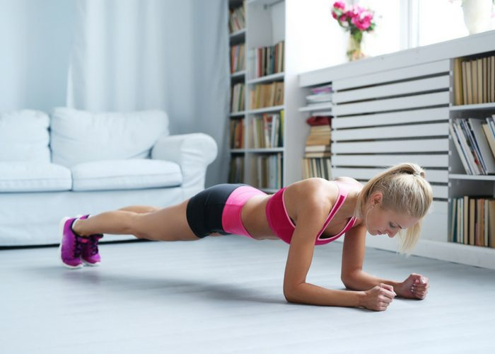 Young woman doing low plank bodyweight back exercises