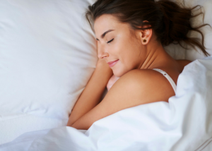closeup of a woman sleeping in bed with white sheets