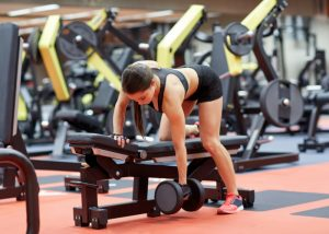 Woman doing dumbbell exercises on a bench at the gym