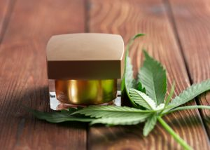 cbd cannabis oil in a square container with cannabis leaves beside it