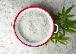 cbd cannabis powder in a red bowl with cannabis leaves beside it