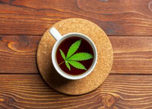marijuana leaf floating in a cup of tea on wooden table