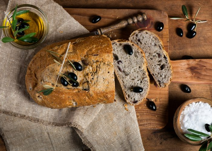 a loaf of casava flour olive bread on a board, slices of olive bread, and a bowl of salt and olive oil on the side