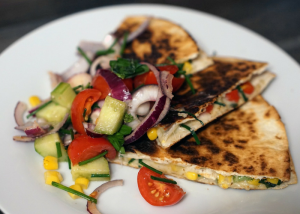 homemade quesadillas filled with vegetables on a white plate