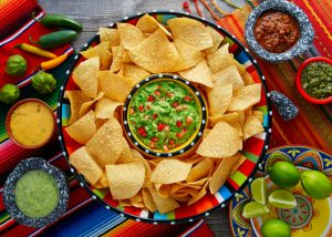 top down view of a big plate of tortilla chips and various dips