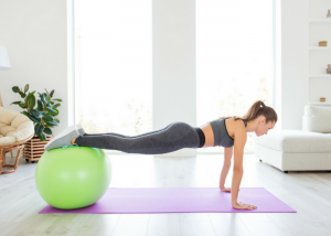 woman with an exercise ball in plank position doing chest exercises at home
