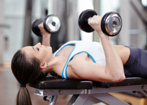 woman doing chest exercises with dumbbells