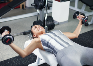 woman smiling and doing chest exercises with weights