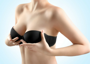 woman in a black bra holding up her breasts