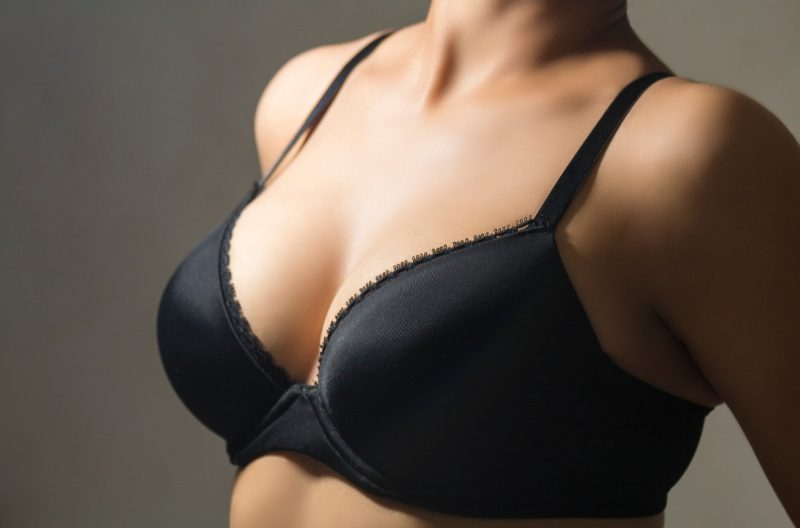 Woman in a black bra with perky breasts from doing chest exercises