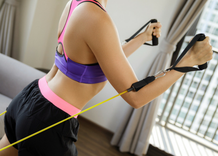 woman doing reverse pectoral fly chest exercises at home with a resistance band