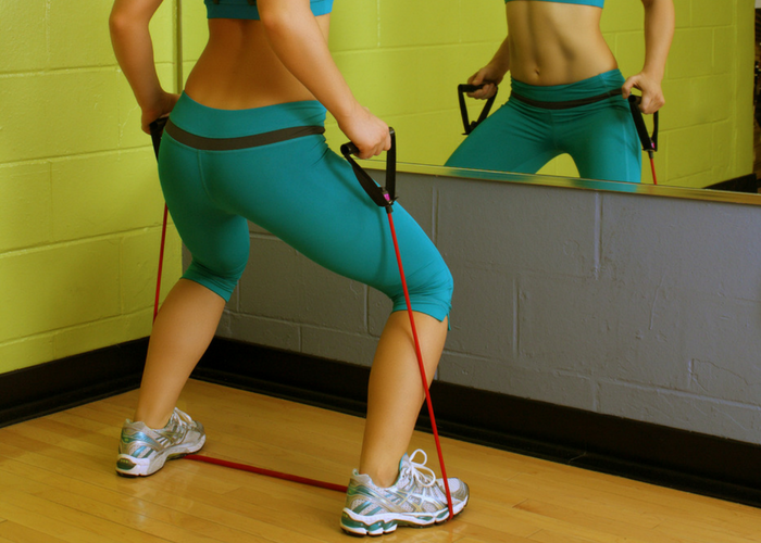woman doing standing raise chest exercise with resistance bands