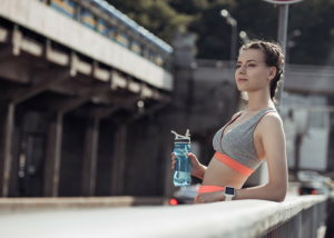 woman in fitness clothes holding a water bottle