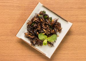 a plate of fried crickets on a wood table