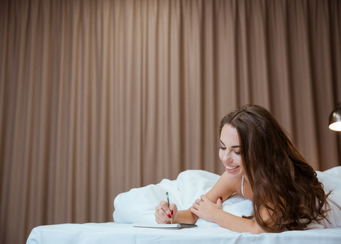 woman in bed writing in her journal