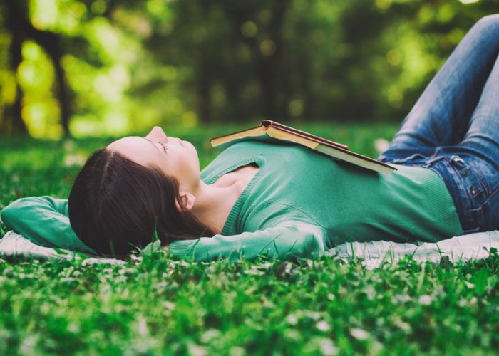 woman lying on the grass with her eyes closed and an open book on her chest
