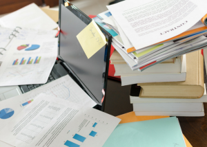 a messy pile of paper documents on a table covering a laptop