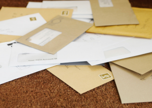 a cluttered pile of mail on a table