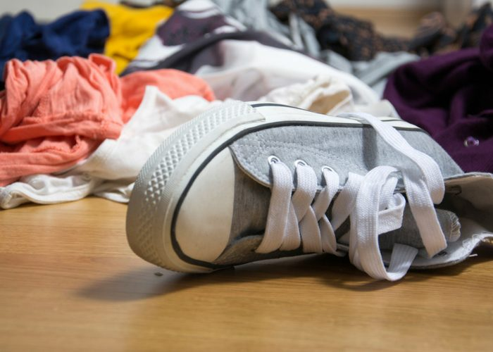 grey shoe on the floor with a messy clutter of clothes behind it
