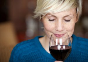 closeup of a woman holding a glass of red wine