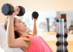 woman doing dumbbell chest exercises at the gym