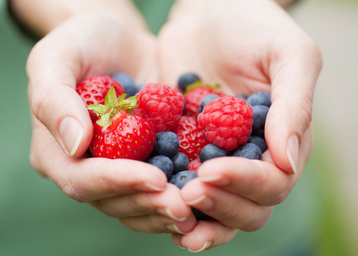 closeup of a woman's hands holding assorted berries