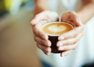 closeup of a woman's hands holding a latte
