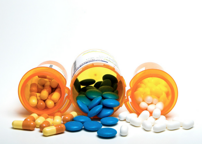 three open bottles of medication with pills pouring out of them