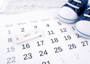 blue baby shoes on a pregnancy calendar