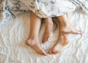 closeup of a couple's feet sticking out from the covers in bed