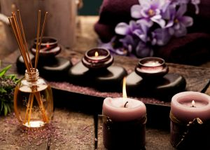 aromatherapy candles and incense with orchids in the background
