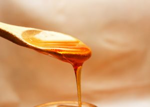 honey dripping from wooden spoon