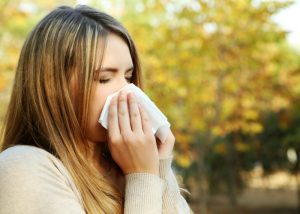 woman with allergies blowing her nose