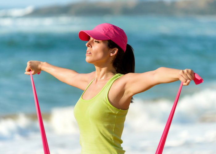 woman working out on the beach with a resistance band