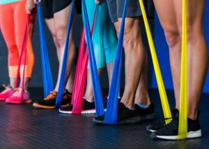 a row of people standing on colorful resistance bands