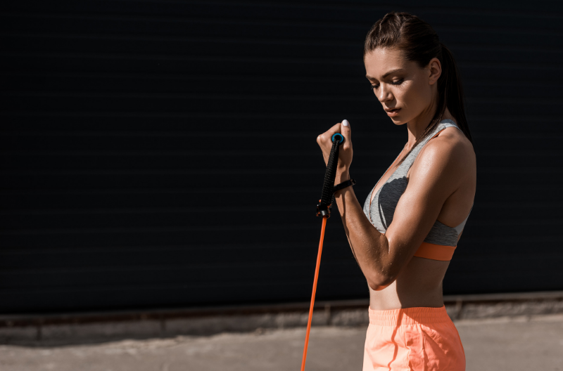 Fit women using resistance band to do bicep exercises