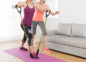 a woman doing resistance band training at home with her trainer