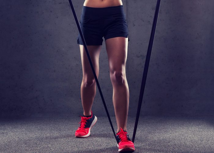 fit woman standing with one foot on a resistance band