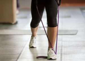 woman doing resistance band training exercises on a tile floor