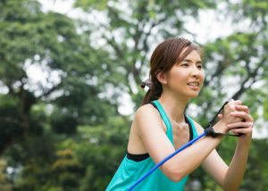 woman in a teal tank top doing resistance band training outdoors