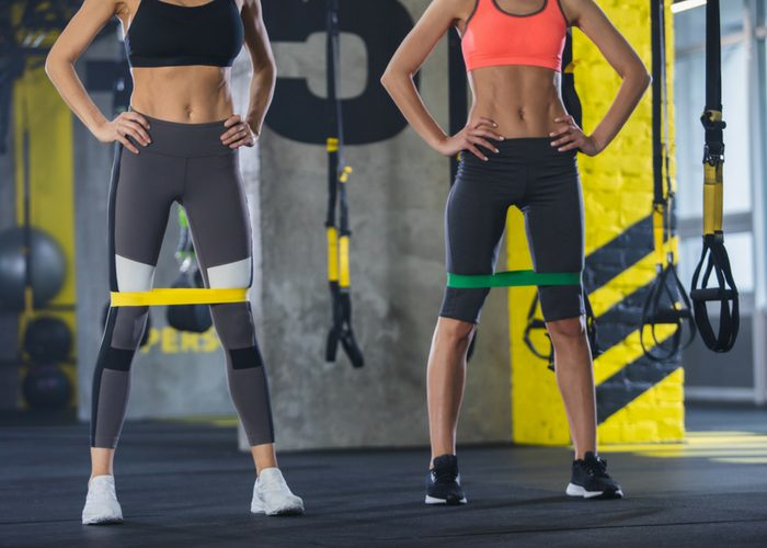 two fit women standing with resistance bands around their thighs