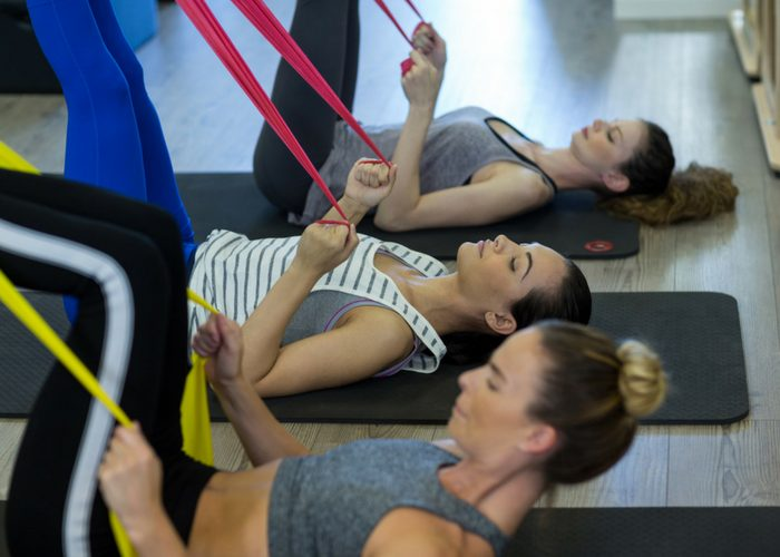 women doing resistance band training on exercise mats in the gym
