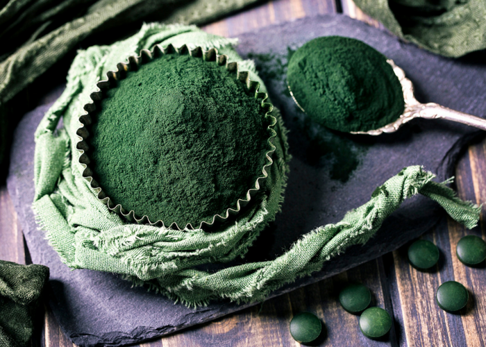 a cupcake tin and tablespoon filled with spirulina powder