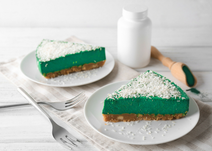 2 slices of green spirulina cheesecake on white plates