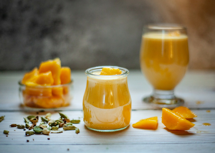 a dish with chopped mangos, a glass of mango smoothie, and a jar of mango smoothie