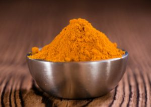 a bowl of heaped turmeric powder on a wooden table