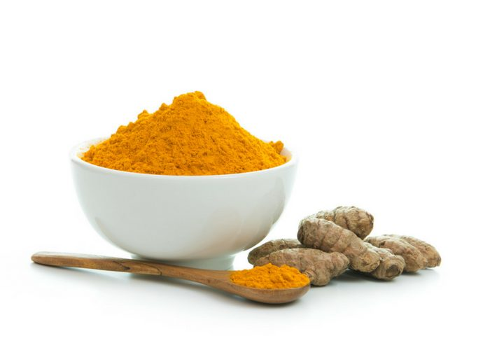 turmeric powder in a white bowl and wooden teaspoon and fresh turmeric on the side
