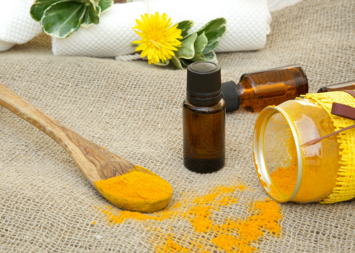 turmeric oil in brown vials, turmeric powder on a wooden spoon and turmeric powder in a jar