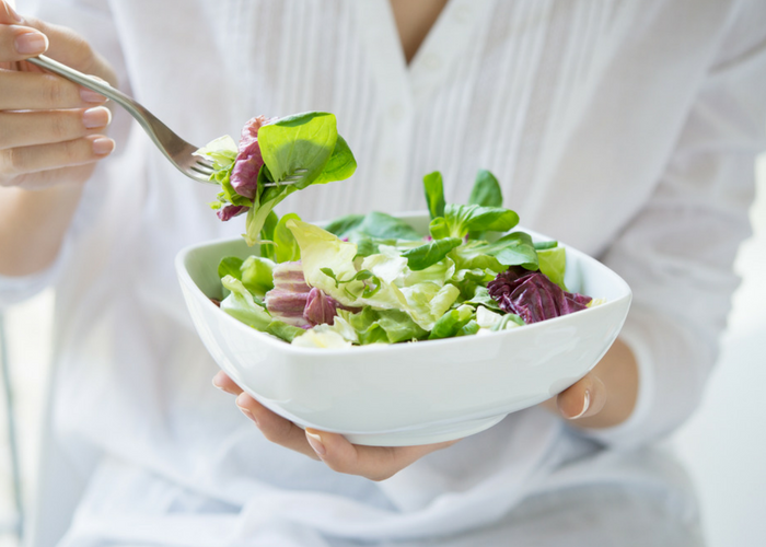 woman holding up a fork and a bowl of green salad